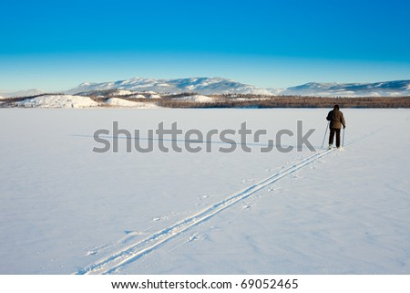 Beautiful cold winter day takes cross-country skiing person out having fun in ski tracks. - stock photo