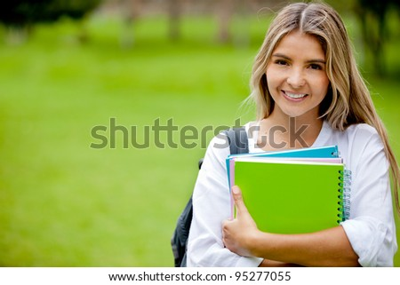 Beautiful college student holding notebooks and smiling - stock photo
