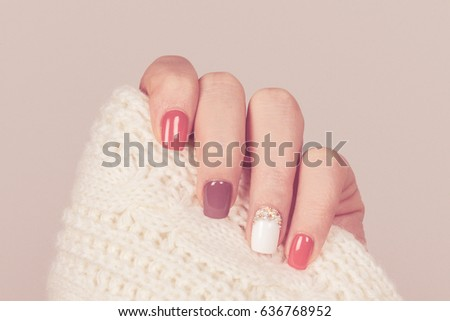 Beautiful colored pastel colors nail polish on hand, closeup. Nail art manicure concept