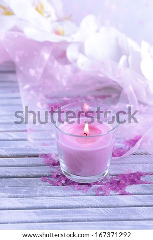 Beautiful colorful candles and  orchid flowers, on color wooden background - stock photo