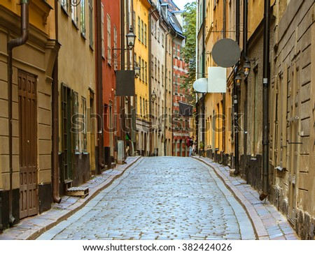 Beautiful colorful Cobbled street in Old Town of Stockholm,Sweden,Gamla Stan.Color street with cobblestone road,orange,yellow houses and streetlights,street light.Summer time.Perspective of the street - stock photo