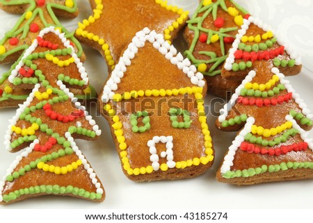 Beautiful colorful decorated Christmas gingerbread cookies. Christmas trees, star and home on white plate - stock photo