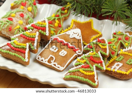 Beautiful colorful decorated gingerbread cookies - Christmas trees and houses with spruce branches - stock photo