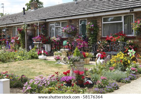 Beautiful colorful garden with a variety of flowers and hanging baskets - stock photo