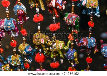 Beautiful colorful handmade wind chimes with bells and decorated toy elephant model hanging in a local store in Rajasthan India. Decorative hangings with mirror and bead work in an Indian shop.