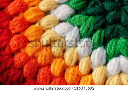 Beautiful colorful handmade woolen fabric closeup photo. The colors of the cloth include red, orange, yellow, green and pink. - stock photo