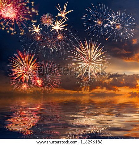 Beautiful colorful holiday fireworks in the evening sky with reflection and majestic clouds, long exposure - stock photo
