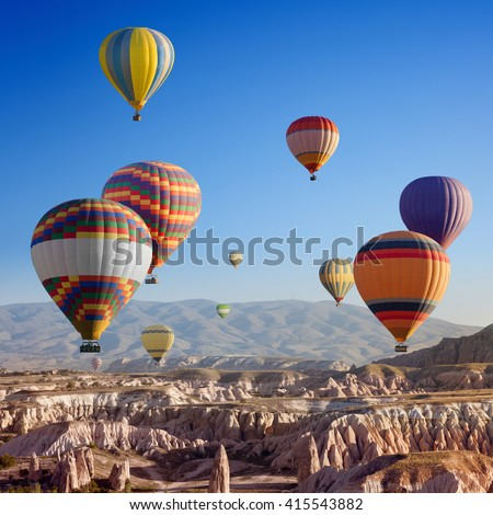 Beautiful colorful hot air balloons flying in clear morning sky above unusual rocky landscape in Cappadocia, Turkey - stock photo