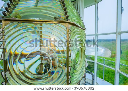 Beautiful colorful Lighthouse along ocean coast close up fresnel lens lighting navigation for ships at sea - stock photo