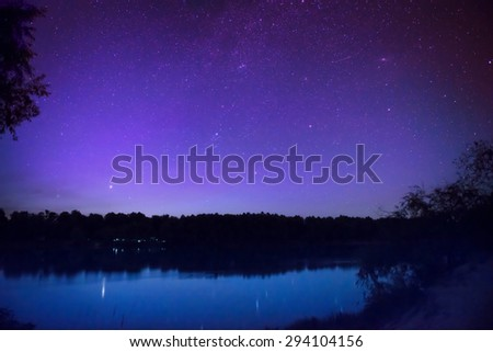 Beautiful colorful night sky with many stars on a lake with forest on the other coast. Milkyway reflection in water - stock photo