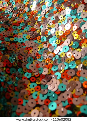 Beautiful, colorful sequins texture pattern in red, yellow, orange and blue. - stock photo