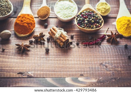 Beautiful colorful spices in wooden spoons on an old brown table. Free space for your text