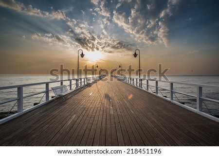 Beautiful colorful Sunrise on the pier at the seaside, Gdynia Orlowo, Poland. Long exposure photography. HDR photo. People on the pier. - stock photo