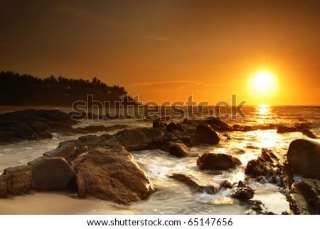 Beautiful colorful sunset over sea and boulders on Sri Lanka - stock photo