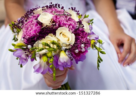 Beautiful colorful wedding bouquet with bride and groom