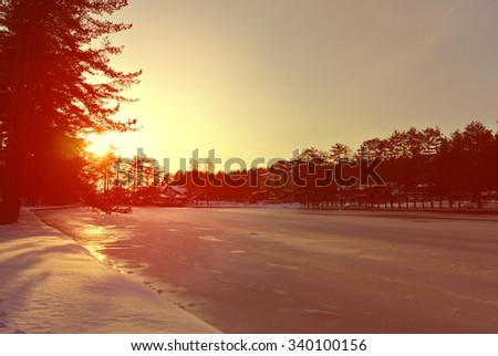 Beautiful colorful winter sunset above frozen mountain lake, with dramatic red sky. Image filtered in faded, washed out, retro style with soft focus and red filter. - stock photo