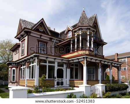 Beautiful colorful wooden Victorian style residential building with porch and balcony on a bright summer spring day. - stock photo