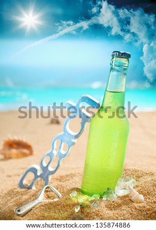 Beautiful composition of chilled beer, beach, bottle opener and amazing sky. Look at my portfolio for more cocktails. - stock photo