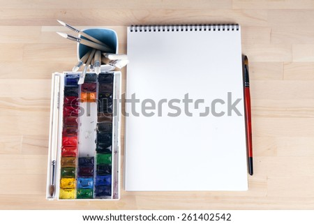 Beautiful composition of watercolor paints, brushes, album artis - stock photo