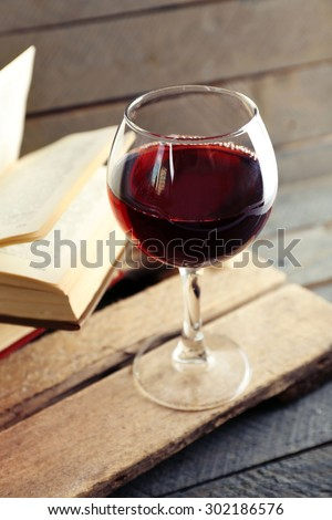 Beautiful composition with glass of wine with old books on table close up