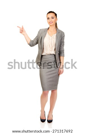 Beautiful confident businesswoman pointing up. - stock photo