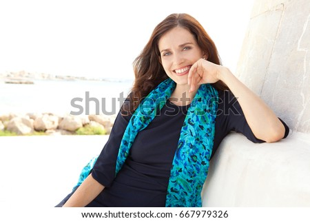 Beautiful confident stewardess sitting relaxing wearing blue uniform clothes, smiling looking at camera in a coastal sea destination, sunny holiday. Travel industry lifestyle, recreation outdoors.