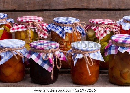 Beautiful conservation of fruits and vegetables in the cellar. Multicolored deevyannyh jars on the old vintage boards. - stock photo