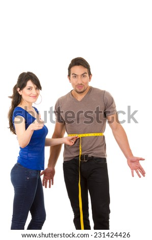 beautiful content girl holding measuing tape around handsome muscular man's fit stomach concept of dieting fitness weightloss - stock photo
