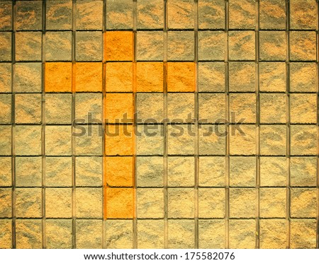 Beautiful contrast of colors between a Christian Cross and the wall - stock photo