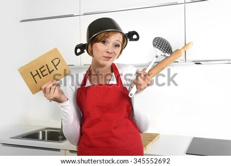 beautiful cook woman confused and frustrated face expression wearing red apron asking for help holding rolling pin and cooking pot on the head at home kitchen in domestic stress and lifestyle concept - stock photo