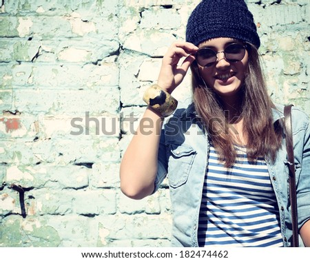 beautiful cool girl in hat and sunglasses against grunge wall, toned - stock photo