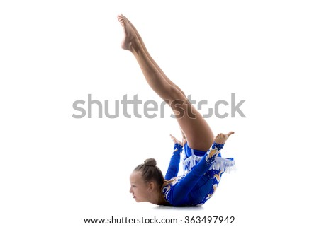 Beautiful cool teenage girl wearing dancer blue leotard working out, dancing, posing, doing art gymnastics, backbend acrobatic exercise, full length, studio, white background, isolated - stock photo
