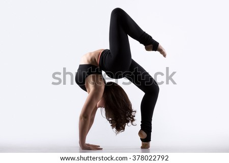 Beautiful cool young fit gymnast athlete woman in black sportswear doing art gymnastics, bridge, backward extension acrobatic exercise on one leg, full length, studio, white background, isolated