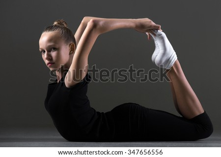 Beautiful cool young fit gymnast athlete woman in sportswear doing art gymnastics, lying in bow posture, backbend acrobatic exercise, full length, studio image, dark background - stock photo