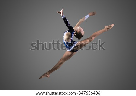 Beautiful cool young fit gymnast woman in blue sportswear dress working out, performing art gymnastics element, jumping, doing split leap in the air, dancing, full length, studio, dark background - stock photo