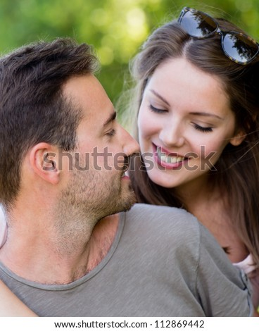 Beautiful couple at the park looking very happy - stock photo
