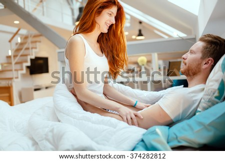 Beautiful couple being romantic and passionate in bed - stock photo