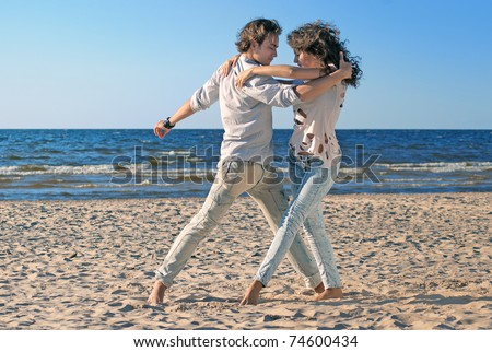 beautiful couple dancing on the beach at the background of the sea - stock photo