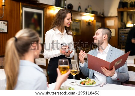 Beautiful couple dining in a restaurant while happy waitress is taking their order - stock photo
