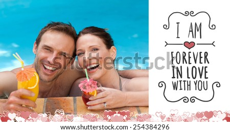Beautiful couple drinking cocktails in the swimming pool against valentines message - stock photo