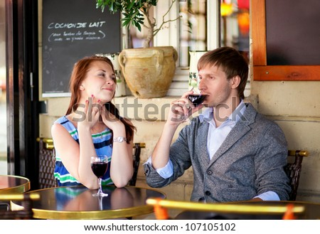 Beautiful couple drinking red wine in a French cafe - stock photo