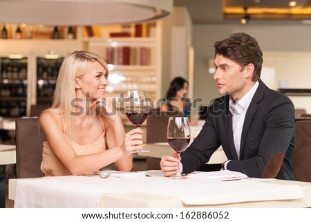 Beautiful couple drinking wine at restaurant. Smiling at each other with romantic feeling  - stock photo