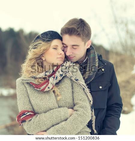 beautiful couple embracing in winter - stock photo