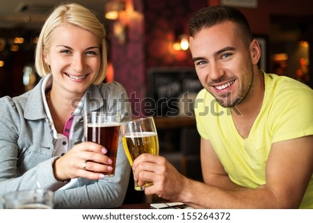 Beautiful couple enjoying beer in a pub - stock photo