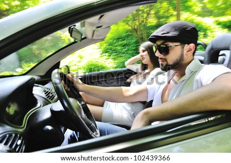 Beautiful couple enjoying nature in a sports car - stock photo