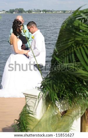 beautiful couple getting married on lake - stock photo