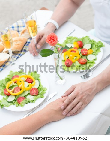 Beautiful couple holding hands and having lunch in the cafe. Man and woman resting in the restaurant near by sea at the beach. - stock photo