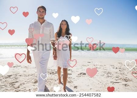 Beautiful couple holding hands and walking towards camera against valentines heart design - stock photo