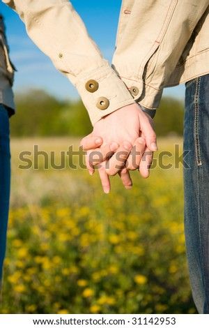 Beautiful couple holding hands on the field - stock photo