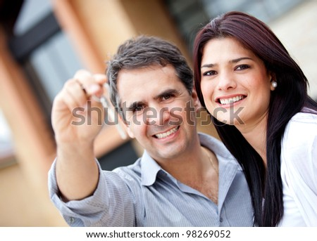 Beautiful couple holding keys and smiling - outdoors - stock photo